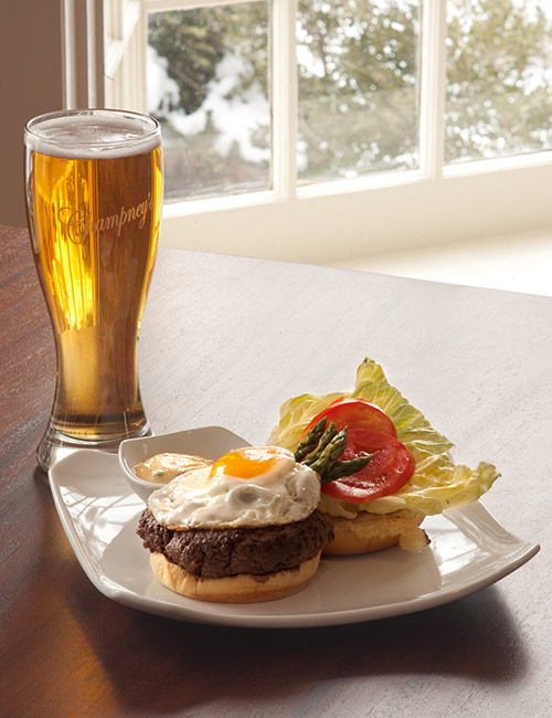 Beer and plate with a burger at Champney's Restaurant