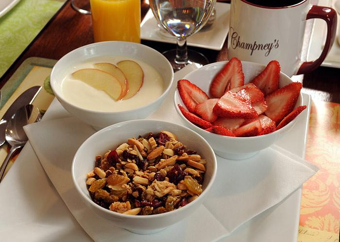Fruit, yogurt, and granola in separate bowls