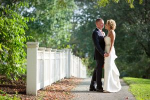 Bride and groom standing on sidewalk