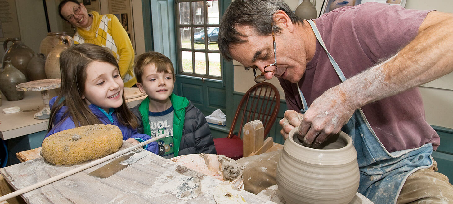 Man showing two kids how to make a clay pot
