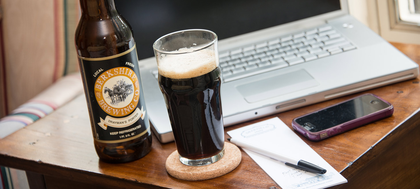 Beer poured into a glass next to the bottle near a laptop