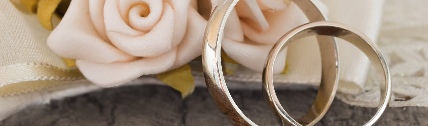 Wedding bands in front of flowers on a wooden table