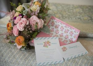 Wedding bouquet and invite sitting on a bed