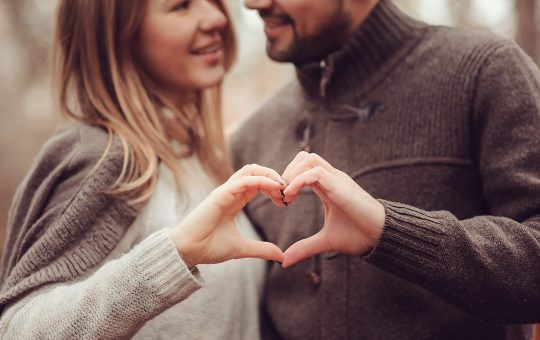 Couple in love making a heart shape with their hands